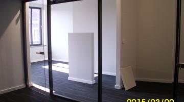 Żaluzje wewnętrzne sterowane elektrycznie zamontowane na przegrodach z drzwiami w wersji całoszklanej.