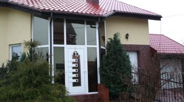 Zabudowa szklana wejścia do domu z drzwiami, wysokość dwóch kondygnacji.