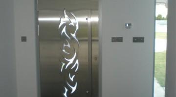 Oryginalne drzwi wejściowe z podświetlanym wzorem wyciętym w panelu z blachy.